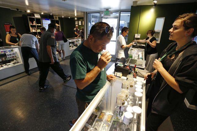 In this Sept. 16, 2015, file photo, customers shop for marijuana inside a recreational marijuana store in Denver. Sen. Elizabeth Warren, D-Mass., is leading a new effort to make sure vendors worki ...