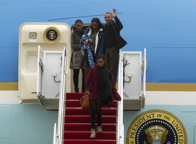 President Barack Obama accompanied by first lady Michelle Obama and his daughters, Malia and Sasha, waves from Air Force One, upon their arrival at Andrews Air Force Base, Md., Jan. 2, 2017. (Jose ...