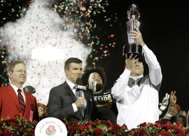 Southern California head coach Clay Helton hold the trophy after their win against Penn State during the Rose Bowl NCAA college football game Monday, Jan. 2, 2017, in Pasadena, Calif. (AP Photo/Ja ...