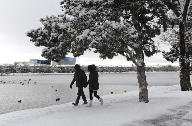 Randy Barr and his girlfriend, Jasmina Jordacevic, walk along the snowy shore of Virginia Lake Thursday, Jan. 5, 2017, in Reno. (Jason Bean/Reno Gazette-Journal via AP)