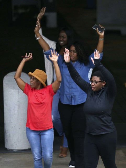 People exit the Fort Lauderdale–Hollywood International Airport  Friday, Jan. 6, 2017, after a gunman opened fire in the baggage claim area at the airport Friday, killing several people and ...