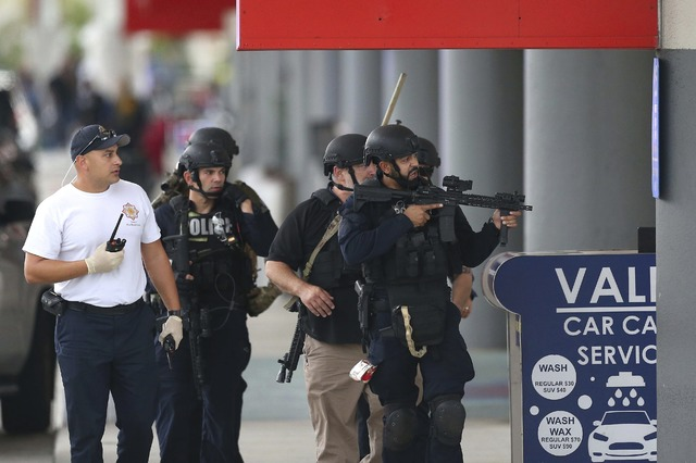 Law enforcement officers walk around Fort Lauderdale-Hollywood International Airport, Friday, Jan. 6, 2017, in Fort Lauderdale, Fla. A gunman opened fire in the baggage claim area at the airport F ...