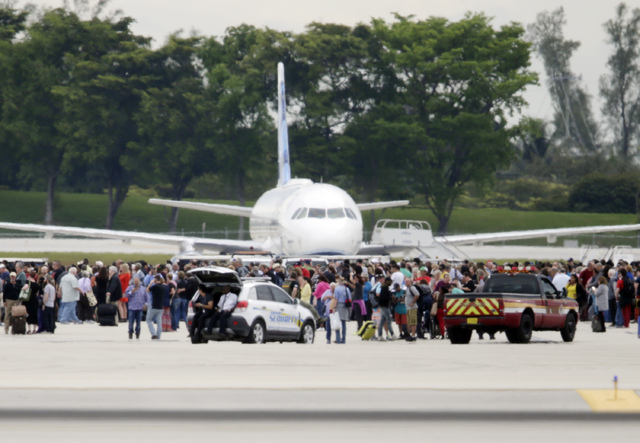 People stand on the tarmac at the Fort Lauderdale-Hollywood International Airport after a shooter opened fire inside a terminal of the airport, killing several people and wounding others before be ...