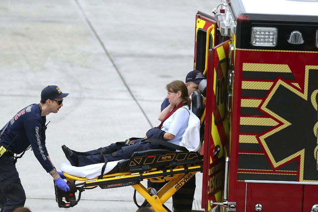 An injured woman is loaded into an emergency vehicle at Fort Lauderdale-Hollywood International Airport after a gunman opened fire inside a terminal of the airport, killing several people and woun ...