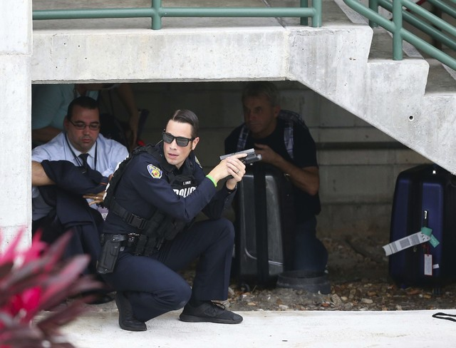 Law enforcement personnel shield civilians outside a garage area at Fort Lauderdale–Hollywood International Airport, Friday, Jan. 6, 2017, in Fort Lauderdale, Fla., after a shooter opened f ...