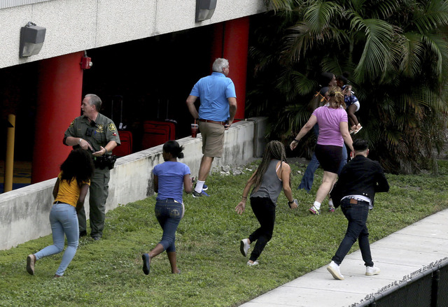 Pople flee the area outside the Fort Lauderdale-Hollywood International airport after a shooting took place Friday, Jan. 6, 2017 in Fort Lauderdale, Fla. A gunman opened fire in the baggage claim  ...