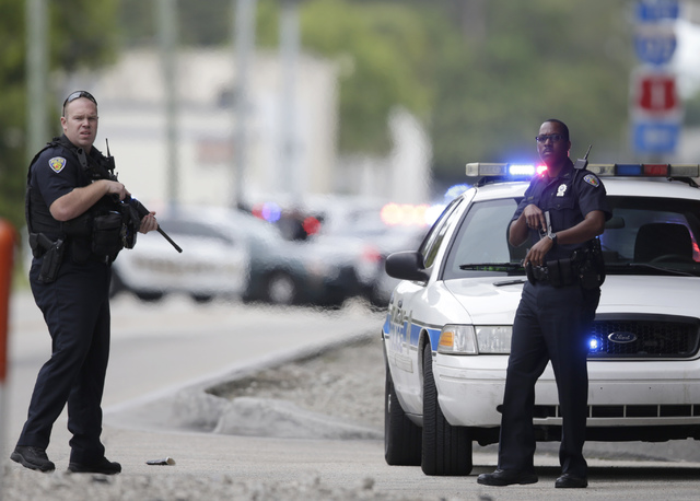 Police officers stand on the perimeter road along the Fort Lauderdale-Hollywood International Airport after a shooter opened fire inside a terminal of the airport, killing several people and wound ...