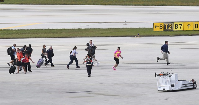 Passengers run on the tarmac at Fort Lauderdale-Hollywood International Airport, Friday, Jan. 6, 2017, in Fort Lauderdale, Fla.   A gunman opened fire in the baggage claim area at the airport Frid ...