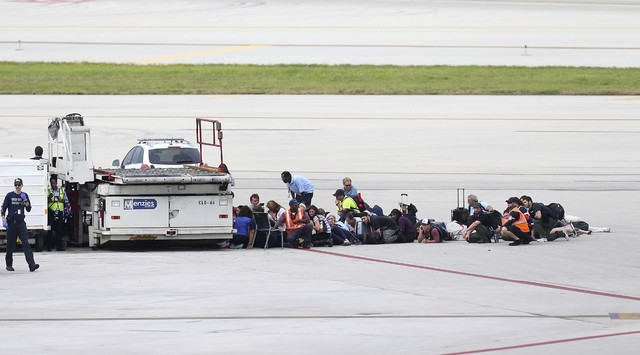 Passengers wait on the tarmac at Fort Lauderdale-Hollywood International Airport, Friday, Jan. 6, 2017, in Fort Lauderdale, Fla.   A gunman opened fire in the baggage claim area at the airport Fri ...