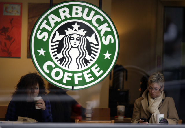In this file photo, customers drink coffee and check messages inside a Starbucks Coffee store in downtown Indianapolis. (Michael Conroy/AP)