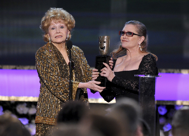 FILE- In this Jan. 25, 2015, file photo, Carrie Fisher, right, presents her mother Debbie Reynolds with the Screen Actors Guild life achievement award at the 21st annual Screen Actors Guild Awards ...
