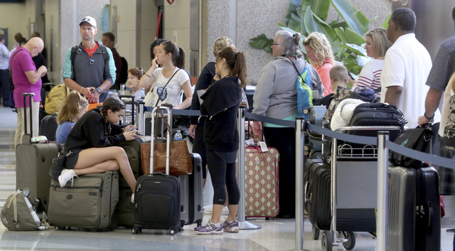 Passengers wait in the departure line at terminal 2 Saturday, Jan. 7, 2017, after the airport re-opened. Investigators continued their work downstairs in the baggage area of terminal 2 at Ft. Laud ...