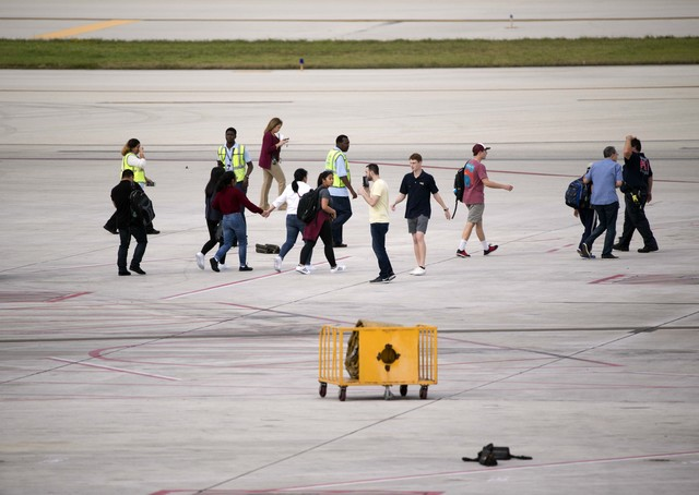 People are shown on the tarmac at Fort Lauderdale–Hollywood International Airport, Friday, Jan. 6, 2017, in Fort Lauderdale, Fla. A gunman opened fire in the baggage claim area at the airport Fr ...