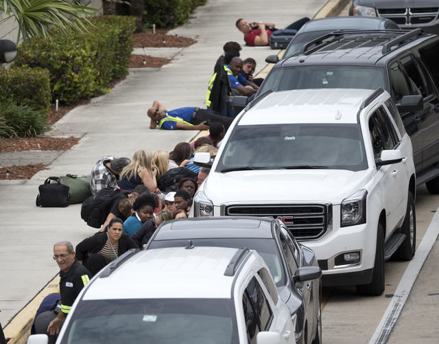 People take cover outside Fort Lauderdale–Hollywood International Airport, Friday, Jan. 6, 2017, in Fort Lauderdale, Fla., after a shooter opened fire inside a terminal of the airport, killing s ...