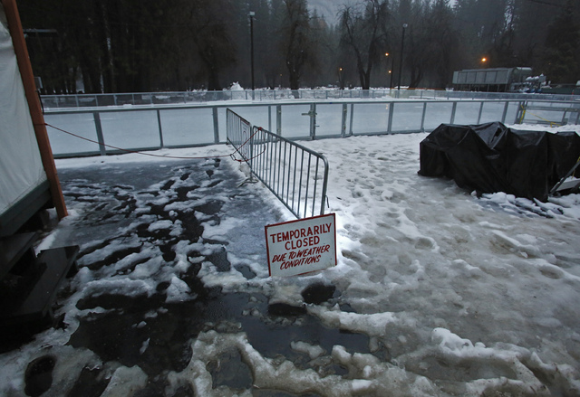 "A ""closed"" sign stands at the entrance of a normally busy ice rink at the Half Dome Village of Yosemite National Park, Calif., on Saturday, Jan 7, 2016. The area has been evacuat ..."