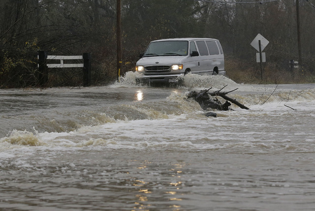 A van drives through flooded water on Green Valley Road in Graton, Calif., Saturday, Jan. 7, 2017. On the California coast, weather forecasters anticipate a storm surge from the Pacific called an  ...