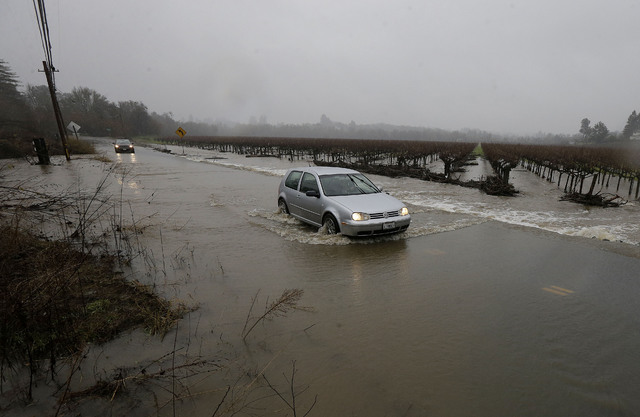A car drives through flooded water on Green Valley Road in Graton, Calif., Saturday, Jan. 7, 2017. On the California coast, weather forecasters anticipate a storm surge from the Pacific called an  ...