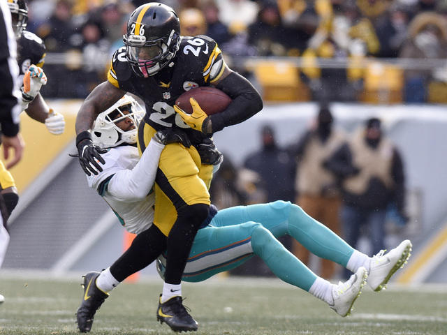Pittsburgh Steelers running back Le'Veon Bell (26) runs through a tackle by Miami Dolphins free safety Bacarri Rambo during the first half of an AFC wild-card NFL football game in Pittsburgh, Sund ...