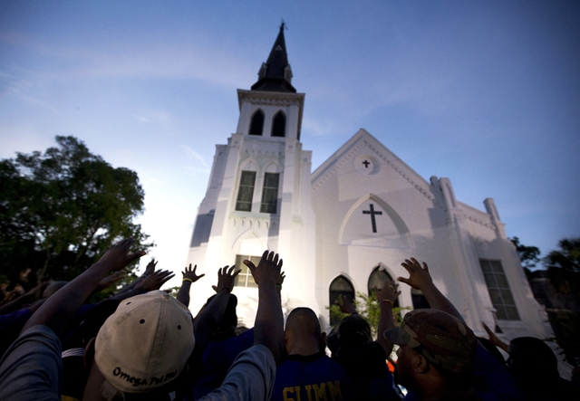 In this Friday, June 19, 2015, file photo, the men of Omega Psi Phi Fraternity Inc. lead a crowd of people in prayer outside the Emanuel AME Church, after a memorial for the nine people killed by  ...