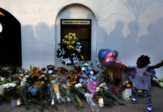 In this Thursday, June 18, 2015, file photo, mourners pass by a make-shift memorial on the sidewalk in front of the Emanuel AME Church following a shooting by Dylann Roof in Charleston, S.C. A fed ...