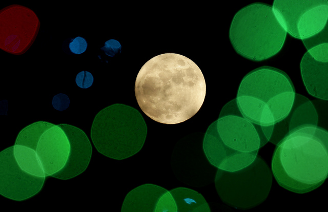 A nearly-full moon is seen among Christmas lights Thursday, Dec. 24, 2015, at a holiday display near Lenexa, Kan. Israeli scientists reported Monday, Jan. 9, 2017, that rather than one giant impac ...
