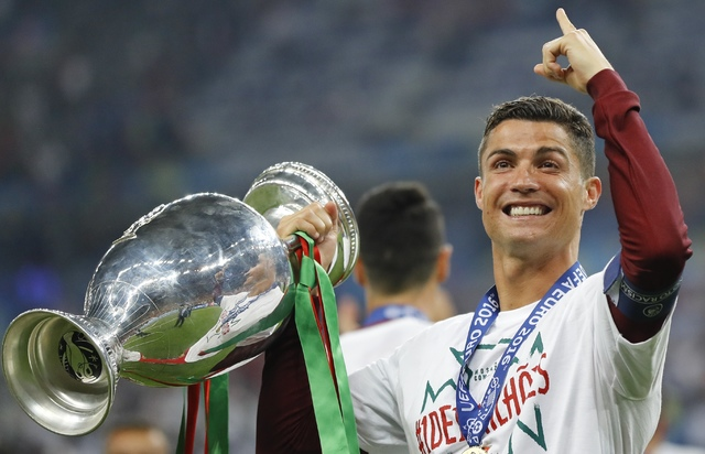 In this Sunday, July 10, 2016 file photo, Portugal's Cristiano Ronaldo celebrates with the trophy at the end of the Euro 2016 final soccer match between Portugal and France at the Stade de France  ...