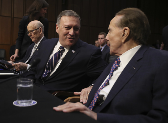 CIA Director-designate Rep. Michael Pompeo, R-Kan. talks to former Senate Majority Leader Bob Dole right, during his confirmation hearing on Capitol Hill in Washington, Thursday, Jan. 12, 2017. be ...