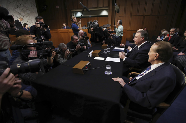 CIA Director-designate Rep. Michael Pompeo, R-Kan., flanked by former Senate Majority Leader Bob Dole, right, and Sen. Pat Roberts, R-Kan., prepares to testify on Capitol Hill in Washington, Thurs ...