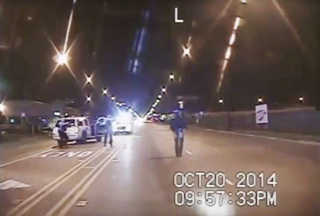 In this Oct. 20, 2014, frame from dash-cam video provided by the Chicago Police Department, Laquan McDonald, right, walks down the street moments before being fatally shot by CPD officer Jason Van ...