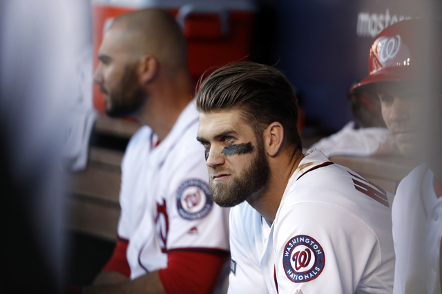 In this photo taken Oct. 9, 2016, Washington Nationals right fielder Bryce Harper (34) sits in the dugout during Game 2 of baseball's National League Division Series against the Los Angeles Dodger ...