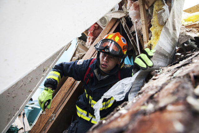 A rescue worker searches inside a mobile home Monday, Jan. 23, 2017, in Big Pine Estates that was damaged by a tornado, in Albany, Ga. Fire and rescue crews were searching through the debris Monda ...