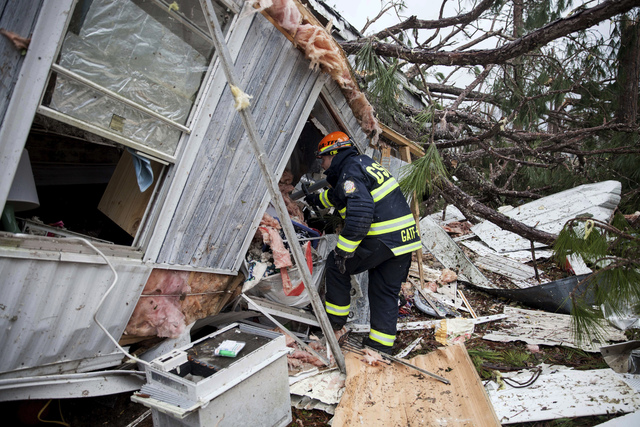 A rescue worker enters a hole in the back of a mobile home Monday, Jan. 23, 2017, in Big Pine Estates that was damaged by a tornado, in Albany, Georgia. Fire and rescue crews were searching throug ...
