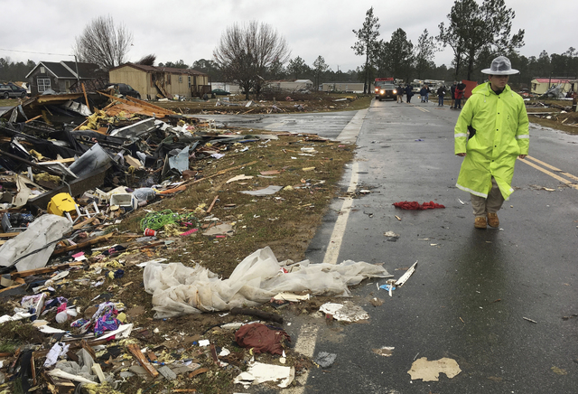 ADDS DATE - A Georgia state trooper walks past a mobile home destroyed by severe weather in Adel, Ga., Monday, Jan. 23, 2017. Gov. Nathan Deal declared a state of emergency in several counties, in ...