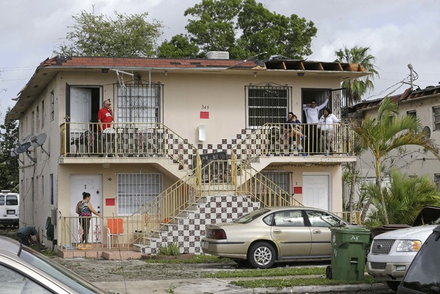 Residents wait to be relocated after their building was declared unsafe after a tornado destroyed the roof of the building Monday, Jan. 23, 2017, in Hialeah, Fla. The storm system that caused dest ...