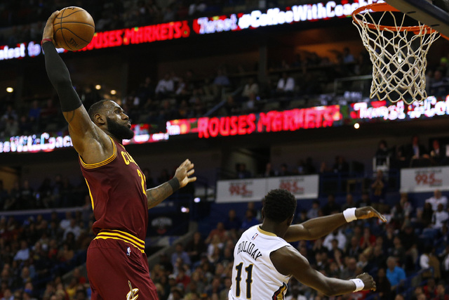 Cleveland Cavaliers forward LeBron James, left, dunks the ball over New Orleans Pelicans guard Jrue Holiday (11) during the first half of an NBA basketball game, Monday, Jan. 23, 2017, in New Orle ...