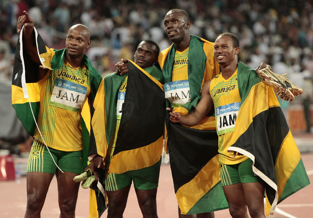 Jamaica's gold medal winning relay team, Usain Bolt, 2nd right, Michael Frater, right, Asafa Powell, left, and Nesta Carter, celebrate after the men's 4x100-meter relay final during the athletics  ...