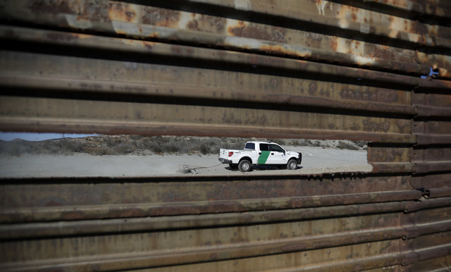 A Border Patrol vehicle drives by in Tecate, Calif., seen through a hole in the metal barrier that lines the border in Tecate, Mexico, Nov. 9, 2016. (Gregory Bull/AP)