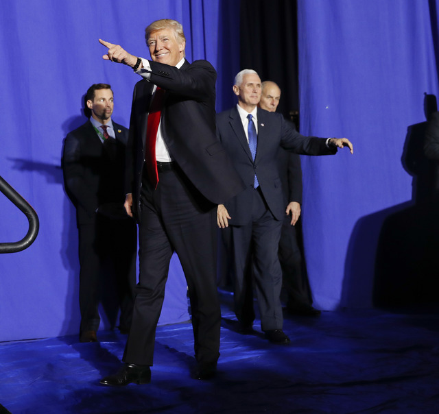 President Donald Trump, accompanied by Vice President Mike Pence, center, and Homeland Security Secretary John F. Kelly, right, gestures as he is introduced before speaking at the Homeland Securit ...