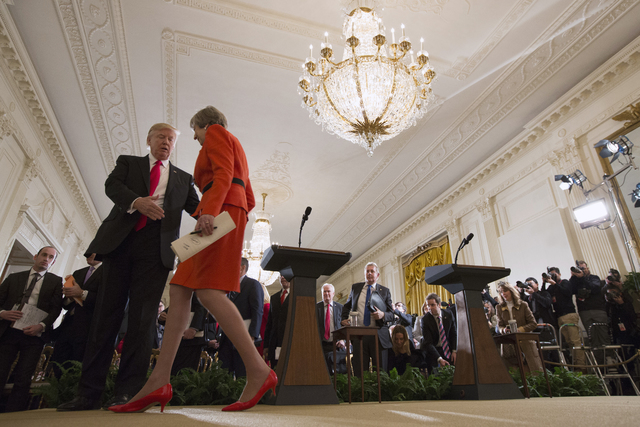 President Donald Trump reaches out to shake hands with British Prime Minister Theresa May after a news conference in the East Room of the White House in Washington, Friday, Jan. 27, 2017. (Evan Vu ...