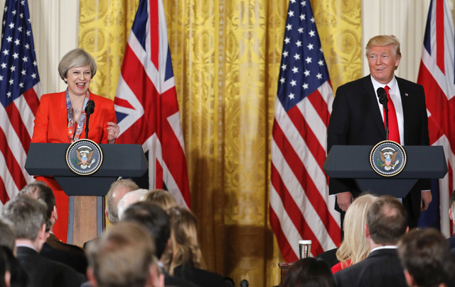President Donald Trump and British Prime Minister Theresa May react to a question from a member of the media during their joint news conference at the White House in Washington, Friday, Jan. 27, 2 ...