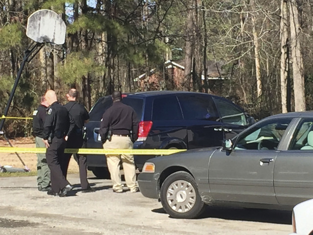 Kinston Police Department officers stand beside a Nissan van and a worn basketball hoop outside a duplex Friday morning Jan. 27, 2017, in Kinston, N.C. Police in North Carolina say former North Ca ...