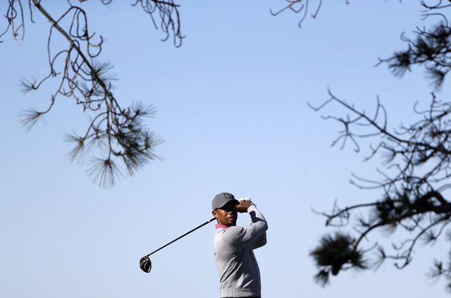 Tiger Woods watches his tee shot on the 17th hole during the second round of the Farmers Insurance Open golf tournament Friday, Jan. 27, 2017, at Torrey Pines Golf Course in San Diego. (Gregory Bu ...