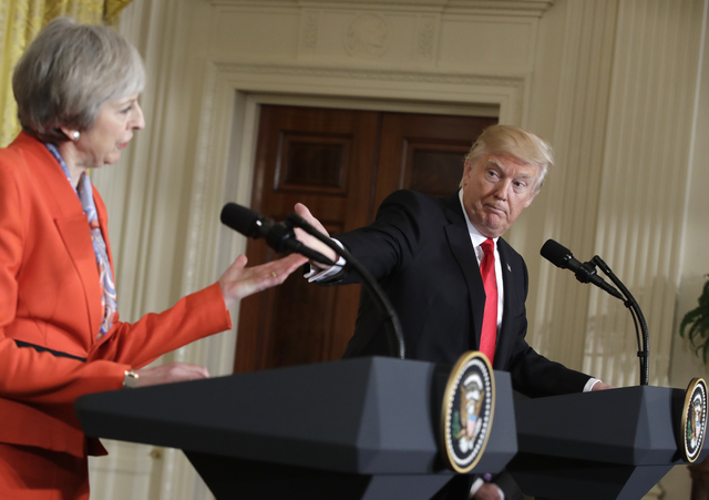President Donald Trump gestures toward British Prime Minister Theresa May during their news conference in the East Room of the White House in Washington, Friday, Jan. 27, 2017.  (AP Photo/Evan Vucci)