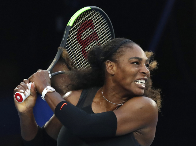 United States' Serena Williams follows through on a backhand return to her sister Venus during the women's singles final at the Australian Open tennis championships in Melbourne, Australia, Saturd ...