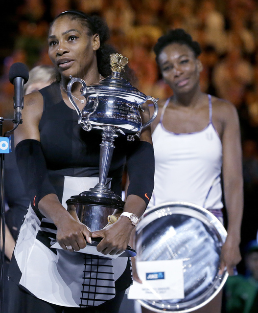 United States' Serena Williams, left, holds her trophy after defeating her sister, Venus, right, in the women's singles final at the Australian Open tennis championships in Melbourne, Australia, S ...