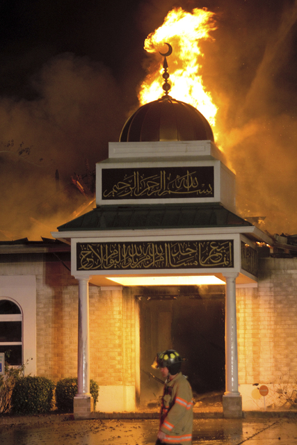 A firefighter walks in front of the Islamic Center of Victoria on Saturday, Jan. 28 in Victoria, Texas.  The early-morning fire Saturday destroyed the mosque that was a target of hatred several ye ...