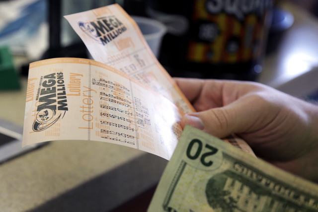 Scott Hoormann holds two Mega Millions lottery tickets he purchased at Energy Express Monday, Dec. 16, 2013, in St. Louis. (AP Photo/Jeff Roberson)