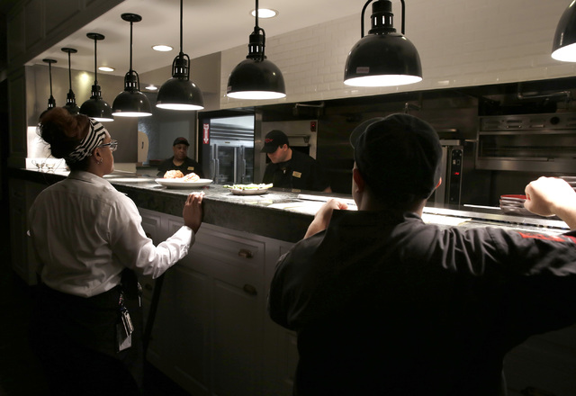 Waitress Whitney Sullivan, left, waits for orders as sous chef Cesar Rodriguez looks on at The Angry Butcher Steakhouse at Sam's Town hotel-casino, Friday, Dec. 23, 2016 in Las Vegas. (David Guzma ...