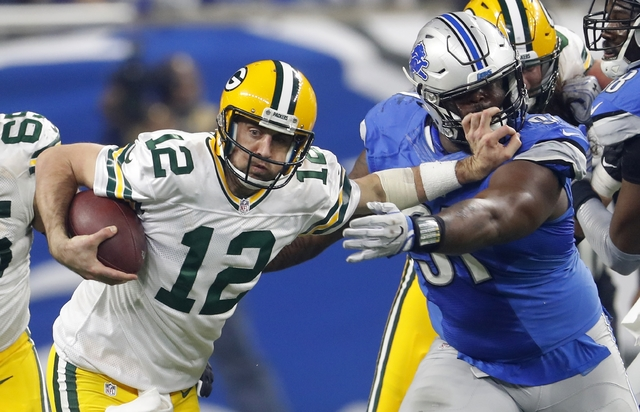 Green Bay Packers quarterback Aaron Rodgers (12) stiff arms Detroit Lions defensive tackle A'Shawn Robinson (91) during the second half Sunday, Jan. 1, 2017, in Detroit. (AP Photo/Paul Sancya)