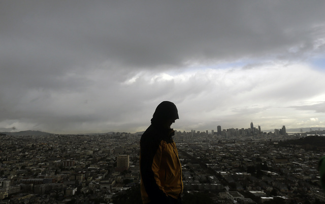 A man walks along Bernal Heights Hill in San Francisco, Monday, Jan. 23, 2017. The tail end of a punishing winter storm system lashed California with thunderstorms and severe winds Monday after br ...